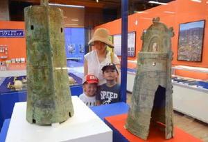 大岩山遺跡(滋賀県野洲市)から出土した銅鐸に見入る来場者=吉野ケ里歴史公園