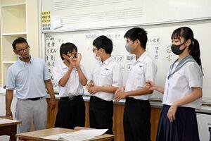 言葉を用いずにジェスチャーで表現する生徒たちと坂本和也さん(左)=唐津市の肥前中