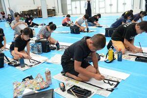 七夕席書会で真剣に筆を運ぶ参加者たち=有田町の焱の博記念堂