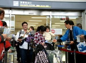 東京から佐賀空港に到着し、佐賀海苔のプレゼント受ける帰省客ら=29日午前10時ごろ、佐賀市川副町の佐賀空港