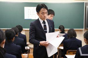 特色選抜試験で問題用紙を配る学校職員=佐賀市の致遠館高