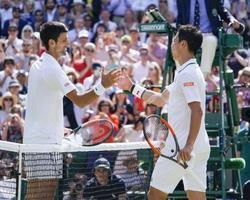 テニスのウィンブルドン選手権、男子シングルス準々決勝でノバク・ジョコビッチ(左)に敗れ握手を交わす錦織圭=11日、ロンドン郊外のオールイングランド・クラブ(共同)