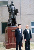 ガリレオ像の前で、佐賀大学の宮崎耕治学長(左)と制作者の德安和博教授=佐賀市の佐賀大学