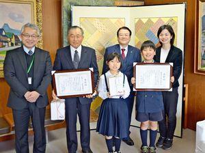 表彰状を受け取った市ラムサール条約推進協議会の宮崎憲治会長(左から2人目)と古枝小の児童ら=鹿島市役所