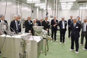 ピックルスコーポレーション西日本の佐賀工場で、生産設備などを見学する関係者=三養基郡みやき町白壁