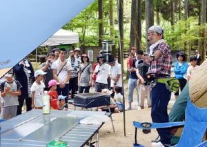 キャンプ用具の説明を聞く家族連れ=佐賀市の北山キャンプ場