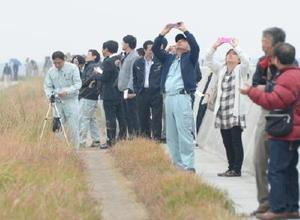 佐賀空港の南側でオスプレイを見つめる漁業者ら=8日午前10時40分ごろ、佐賀市川副町