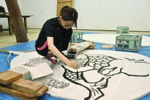 大きなうちわに墨で「アマビエ」を描く天山ものづくり塾の古賀百葉さん=小城市小城町の小柳酒造