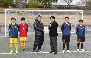 松田一也町長にサッカーゴールの目録を送る上曽山拓史・FCソレイユ理事長(左から3人目)=基山総合公園多目的グラウンド