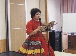 パラシュートスカートをはき踊りを指示する芦刈由美子さん
