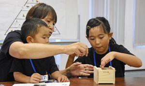 間伐材を使って貯金箱を作る参加者=佐賀市のニッセイ・ライフプラザ佐賀
