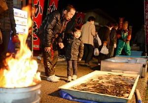 フナが入った水槽を興味深くのぞき込む男の子=鹿島市浜町の酒蔵通り(撮影・鶴澤弘樹)