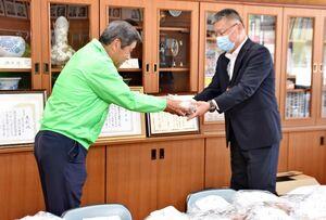 山口校長(右)に布マスクを手渡す嬉野小校区地域コミュニティ運営協議会の嬉野会長=嬉野市の同校