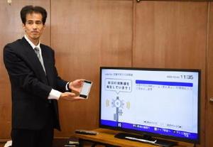 防災行政無線の内容が確認できるテレビ画面とスマートフォンでも音声がきけることを説明するケーブルワンの前田雄次さん=武雄市役所