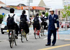 自転車利用者に一列で走行するよう呼び掛ける警察官=佐賀市の佐賀工高付近