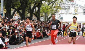 50メートル競走で小学生と勝負するウォルシュ・ジュリアン選手(中央)=佐賀市の本丸通り
