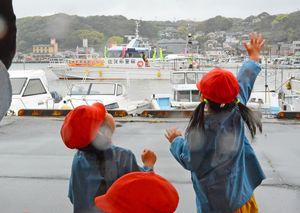 出港する警備艇「はど」を、飛び上がって送り出す園児たち=唐津市呼子町の呼子港