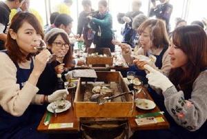 竹崎カキと白ワインの相性を楽しむ女性客ら。「ぐいぐい飲めるし、相乗効果でカキもおいしい」と好評だった=藤津郡太良町の「漁師の館」