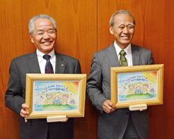 新生児に贈られる木製フォトフレームを手にする佐賀西信用組合の栢森久理事長(左)と夢木香の松尾進社長=鹿島市役所