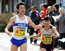 佐賀市の八谷英佑からトップでたすきを受ける吉冨博子(右)=17-18中継所