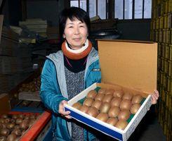 無農薬で生産した本年産のキウイフルーツを掲げる谷口孝子さん=江北町上小田