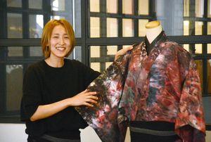 自身がデザインした着物を示しながら話すキサブローさん=佐賀市呉服元町のリフトコーヒー