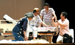 会のメンバーでつくる「劇団くまくま」は在宅医療をテーマにした劇を上演。時にコミカルに、会場を沸かせた=佐賀市のメートプラザ佐賀