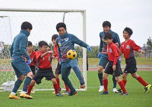 ゴール前まで攻め込むDF安在和樹選手をマークする子どもたち=沖縄県の読谷村陸上競技場