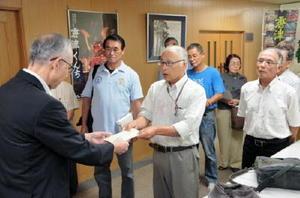 坂井俊之市長の即時辞職を求めて、岡本憲幸副市長(左)に文書を手渡す「唐津をよくする会」の木村眞一郎共同代表(中央)=唐津市役所