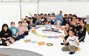 開園20周年を迎え、アーティストのミヤザキケンスケさんとテントに絵を描いた仁比山小の児童たち=吉野ケ里歴史公園