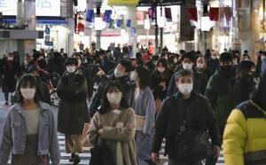 東京・渋谷のスクランブル交差点を行き交うマスク姿の人たち=15日