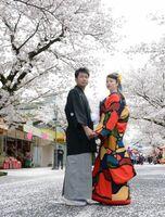 満開の桜の下で、婚約した2人が仲むつまじく記念撮影。春まつりが開催されている祐徳稲荷神社門前商店街=鹿島市古枝