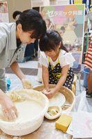 セラミック科の生徒の指導を受けながらろくろ体験する女児=佐賀市のモラージュ佐賀