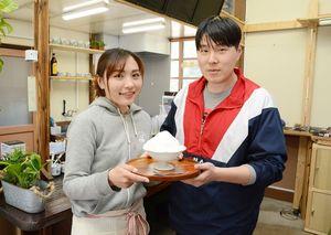 看板商品「粉雪」を手にする金、岩井さん夫妻。JR上有田駅に再オープンしたカフェを営む=有田町の同駅
