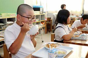 「シギの恩返し米」について学んだ後、おいしくほおばる児童ら=佐賀市の東与賀小学校