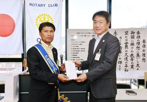 大野敬一郎・小城市教育長(右)に図書カードを贈った小城ロータリークラブの古川博文会長=小城市のゆめぷらっと小城