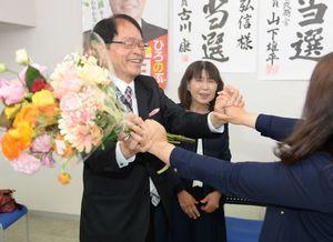 初当選を決め、花束を受け取り、支援に感謝する深浦弘信さん(左)=15日午後11時15分、伊万里市二里町の事務所