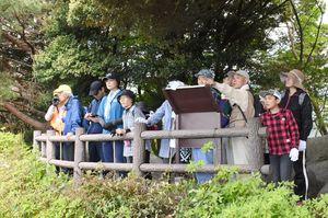 城山山頂にあった勝尾城の「物見岩」から、島津勢が攻めてきたとされる久留米方面を望む参加者=鳥栖市