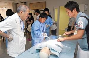 人体に見立てた鶏肉を超音波メスで切開するセミナーに参加した中高生=伊万里市の山元記念病院