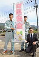 「マニャー」を使った交通安全のぼり旗を作った牟田建設の本山信広さん(左)ら=唐津市厳木町