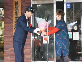 運行終了式で花束を受け取る昭和バスの運転手(左)=佐賀市の三瀬支所