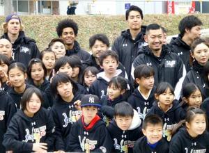 熊本県益城町の仮設住宅を訪問し、地元の児童らと記念撮影するBリーグの選手たち=13日