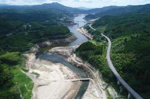 貯水率35%を下回った嘉瀬川ダム。水の引いた一部から、かつての集落跡が姿を現した。奥が佐賀市方面(8月22日、ドローンで撮影)