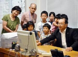パソコンの画面上で為替の仕組みについて解説する松井幹雄佐賀支店長(右)と参加者たち=佐賀市のSMBC日興証券佐賀支店
