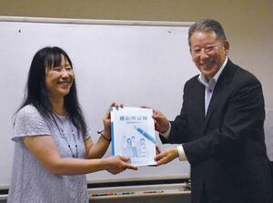 岡村希世子会長(左)に親心の記録を贈る田島広一社長=佐賀市の佐賀大学附属特別支援学校
