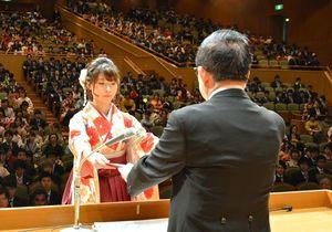 宮﨑耕治学長(右)から学位記を受け取る卒業生=佐賀市文化会館