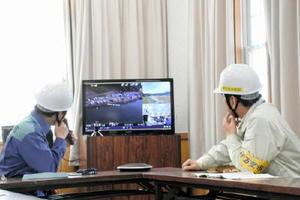 ドローンからの映像で被災状況を確認する塚部芳和市長(左)=伊万里市の黒川公民館