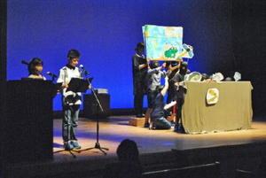 池にすむ生き物たちとレンコンのやりとりを劇にして上演する「須古小親と子の読書会」メンバー=佐賀市の県立美術館ホール