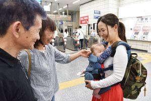Uターンが本格化したJR佐賀駅で、孫との別れを惜しむ祖父母=佐賀市