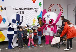 東京五輪のマスコットキャラクターと記念撮影する子どもたち=佐賀市大和町のイオンモール佐賀大和